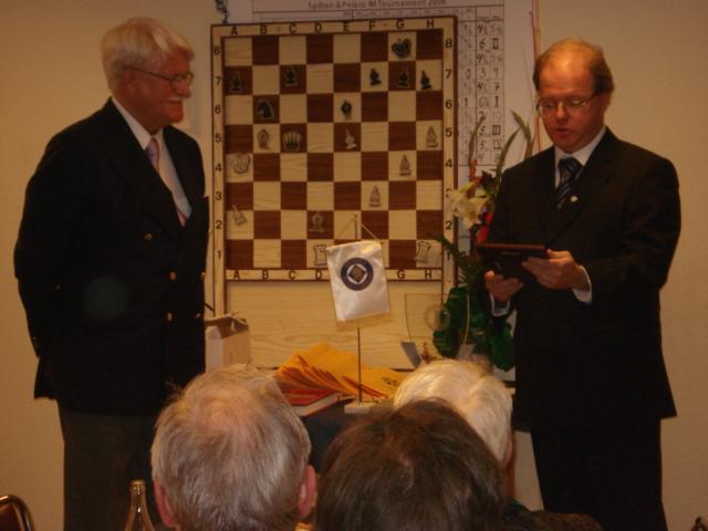En långrandig ordförande gör sig beredd att överlämna hedersplaketten till Lars Borgström (t.v.) vid 100-årsfesten.