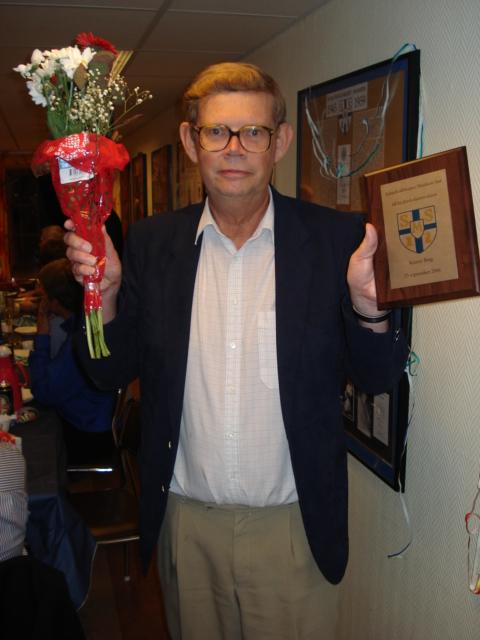 Nye hedersledamoten Krister Berg med blomsterbukett och plakett vid 100-årsfesten.