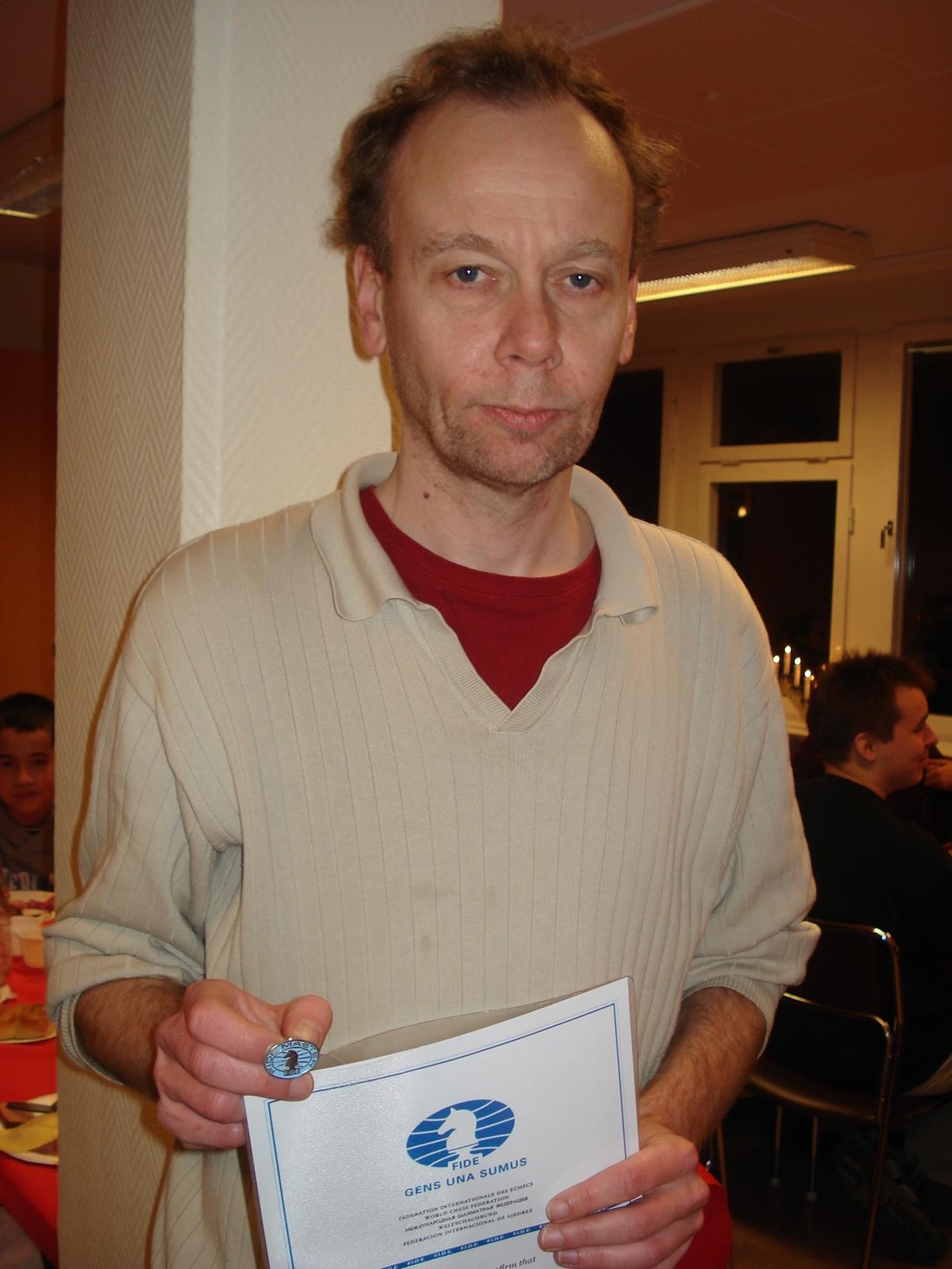 Magnus Carlhammar med nyemottaget FIDE-mästardiplom och dito -nål.